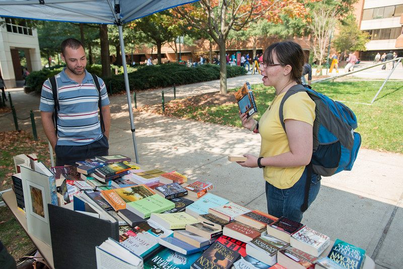 Students stop to talk about books at a book swap hosted by the student staff of Volition Magazine, Mason's undergraduate art and literary journal, during Fall for the Book week at Fairfax campus. Photo by Alexis Glenn/Creative Services/George Mason University