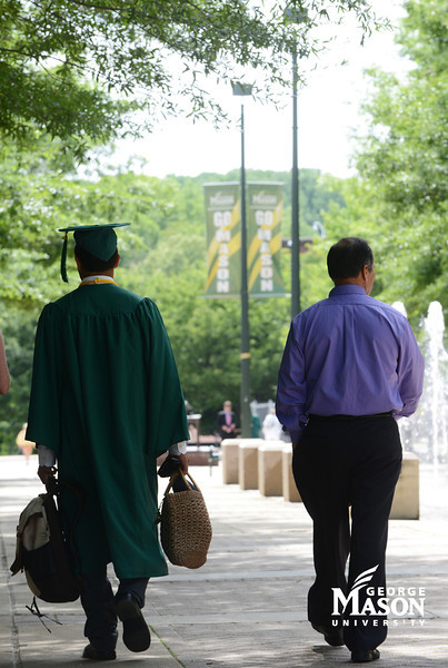 A graduate take one last stroll through campus with family. Photo by Evan Cantwell/Creative Services/George Mason University