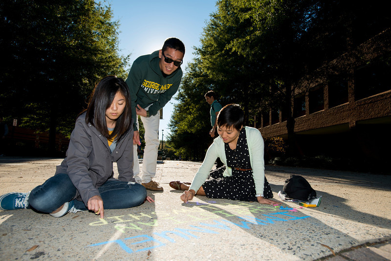 Students from a student club draw an event announcement in chalk on the sidewalk outside Robinson Hall at Fairfax campus. Photo by Alexis Glenn/Creative Services/George Mason University