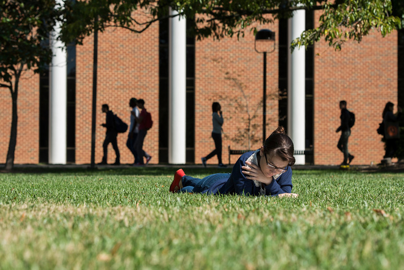 A student reads in the grass near Fenwick Library at Fairfax campus. Photo by Alexis Glenn/Creative Services/George Mason University