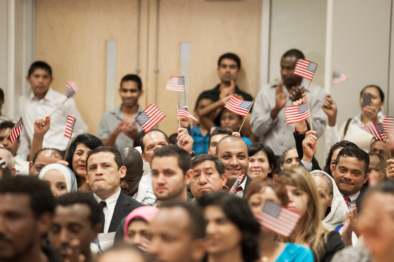 Immigrants wave American flags after they took the Oath of Allegiance to complete their U.S. citizenship process at a naturalization ceremony at Founders Hall at the Arlington campus. Photo by Alexis Glenn/Creative Services/George Mason University