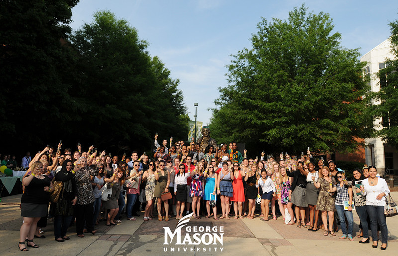 Graduates, families, faculty and staff share in a toast during the GradFest One Last Look event. Photo by Evan Cantwell/Creative Services/George Mason University