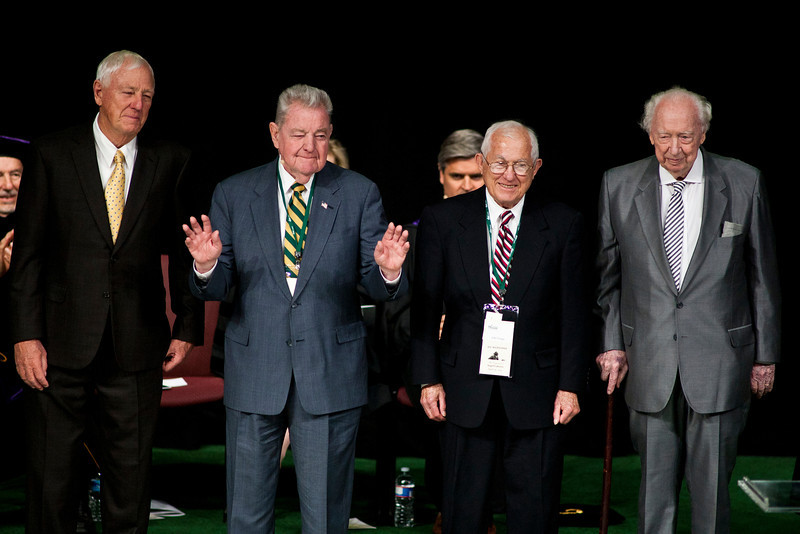 """John T. """"Til"""" Hazel (2nd L) speaks, as (L to R) Milt Peterson, John Toups, and Sidney O. Dewberry listen at the Installation Ceremony of the Inauguration of Ángel Cabrera at the Patriot Center. Photo by Craig Bisacre/Creative Services/George Mason University"""