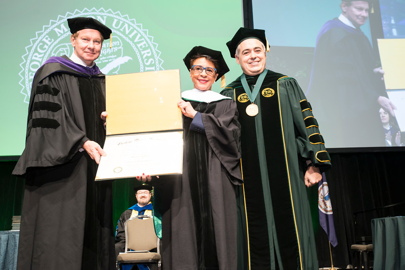 Board of Visitors Rector Tom Davis presents speaker Sheila C. Johnson, Co-Founder, BET; CEO, Salamander Hotels & Resorts, with an honrary degree during 2016 Winter Graduation at the Fairfax Campus.  Ángel Cabrera looks on. Photo by:  Ron Aira/Creative Services/George Mason University