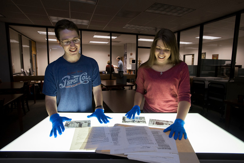 Students Andrew Weisberg and Jessica Campbell, who researched and built he Mason History website, look at historical documents inside the Special Collections Reading Room. Photo by Alexis Glenn/Creative Services/George Mason University