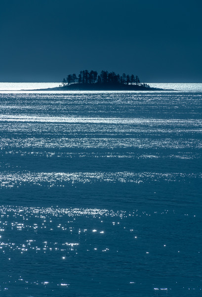 Moonlight illuminates an island in an Alaskan bay