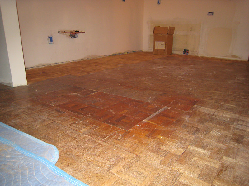 We had a full box of 50 unused parquet tiles in the basement from  when the floor was first installed (in the back against the wall).  Instead of put in a whole new floor, we saved a few $k by reusing and refinishing this floor.  Here it is patched and ready to sand.....