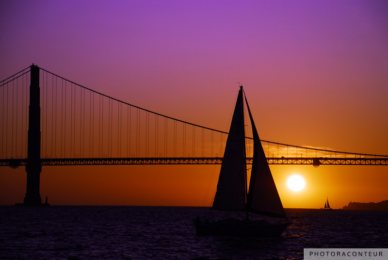 """Sailboat Sunset on the Bay"" ~ It's hard to top watching the sunset behind the Golden Gate Bridge. Until two sailboats line up on either side of the setting sun, that is!  It was a chilly September night as our catamaran tour sailed around Alcatraz and throughout San Francisco Bay. Just minutes after capturing ""Through the Sail"" and passing under the bridge then back again, the sun was just about to dip into the ocean amidst a peach and purple sky when two sailboats lined up on each side -- one near, one far.  Thanks for that, captains."