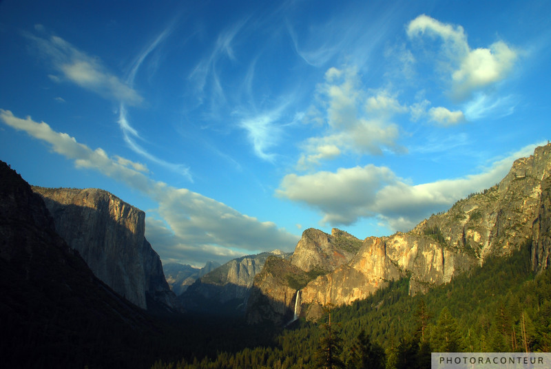 """Yosemite Valley Cloudscape"" ~ View of majestic Yosemite Valley from Inspiration Point near sunset. The view includes El Capitan, Half Dome, and Bridalveil Falls.  This is one of my favorite photos that I've ever taken. I took this photo of the amazing Yosemite Valley in the summer of 2008.  Visiting Yosemite is probably on the 'bucket list' of countless photographers, as it was the home base of the legendary Ansel Adams. It was indeed quite an experience to see in person the beautiful peaks, valleys, and waterfalls that were captured by the skilled eyes and hands of Ansel. His portfolio of Yosemite photos is incredible, especially considering that most of his photos were taken with medium or large format cameras with manual settings. He didn't have the luxury or convenience of automatic digital photography. Ansel couldn't take dozens or even hundreds of images and sort through them later. He could take only two or three exposures of a scene, sometimes only one. Then he would take those negatives into the darkroom and develop them with pure mastery, and with no Photoshop assistance, of course.  Ansel has several famous photos from this same viewpoint within Yosemite National Park. This viewpoint is called ""Tunnel View"", as it is an overlook of the valley just before a 1.5 mile stretch of Wawona Road passes through a tunnel near Turtleback Dome and Bridalveil Fall. From this viewpoint, many of Yosemite's famous features can be seen. El Capitan is on the left, Half Dome near the center along with North Dome, and of course Bridalveil Fall.  I arrived at Tunnel View about an hour or so before sunset in order to find a good spot to take photos. I moved around to several areas before settling on this viewpoint. I watched the sunlight get warmer and drape the valley in increasingly beautiful light. About 15 seconds before this exposure, I noticed a series of wispy clouds traveling through the sky, rather quickly from my right. I immediately adjusted my camera on the tripod such that I could frame the valley along with these unique clouds flying by. As soon as I got my camera adjusted, the clouds appeared in just the right spot as shown and I was able to snap this single exposure. And seconds later, the wispy, curvy cloud formations were gone. I knew immediately that I had captured something special and unique. It was a very Ansel-esque moment, where the light, the clouds, and the scenery all meshed together for one special moment, just for me and my camera."