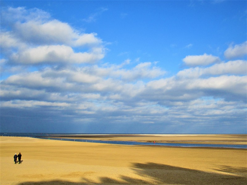 A wide expanse of golden sand beach with white clouds in a blue sky.