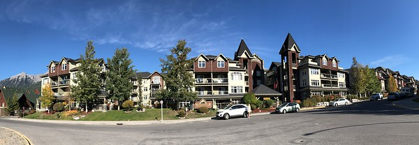 A panorama of the Windtower Mountain Lodge complex as seen as you drive up Montane Road from the roundabout on Hwy 1A.  The road directly in front is Kananaskis Way.  The Windtower extends from the end of the taller building on the left to just beyond the trees on the right.  The main entrance is next to the tall tower in the center.  The entrance to underground parking is on the far left.