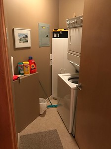 The laundry with stacked washer/dryer.  Cleaners, spare lightbulbs, etc are in the cabinet at the end.  Tool box with some basic tools on top of cabinet.
