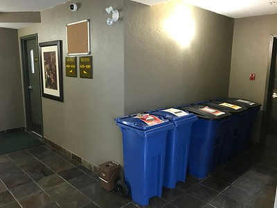4th floor lobby with recycle bins in the side hallway.  The trash chute is behind the door ahead (directly opposite the elevator.