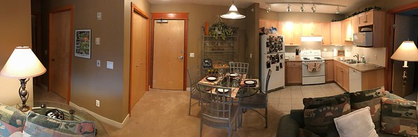 A panorama from the living area.  Master bedroom is on the right and guest room / den is on the left.  2nd bathroom is on the left and laundry is at the end of the small corridor on the left.  Note garage door opener, etc., in the black dish on the small table on the left behind the sofa.