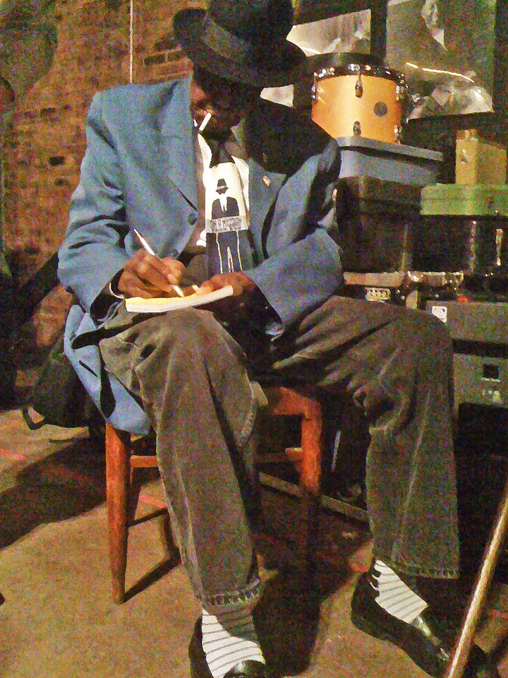 Pinetop Perkins signing a piece of note paper from my friend's little book. Joan Hughes took the photo at Antones in Austin, TX on March 26, 2010, right after the house lights came on between shows. Massaged in Photoshop.