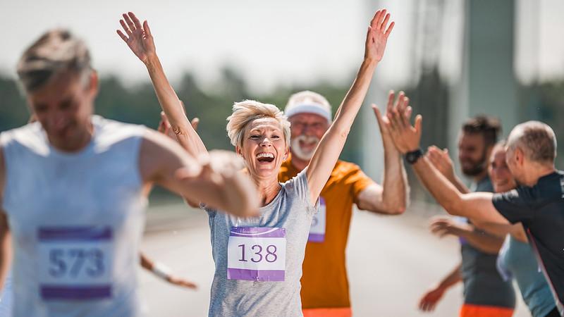 Happy senior woman celebrating her end of marathon race.