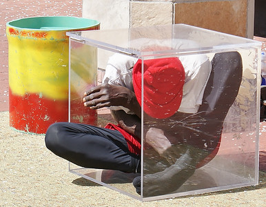 Contortionist performing on the downtown mall in Boulder, Colorado, squeezes himself into a small, clear, plastic box.
