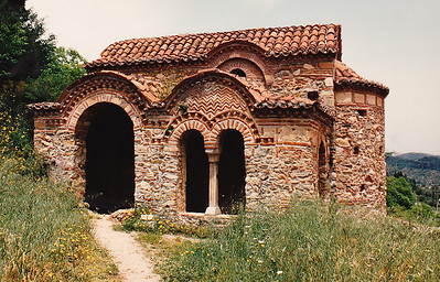 Mystras: Saint George's Chapel (partially restored) located along the Middle City's main path leading from the Peribleptos Monastery to the Despot's Palace. With its barrel-vaulted architecture, this chapel includes built-in cisterns, tombs, and wall frescoes.
