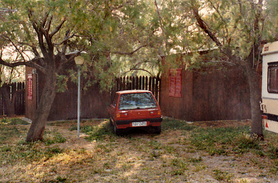 "My rented Fiat parked next to the ""hut"" I rented overnight at the ""Kamping Kreioneri"" travellers camp in Akrata, Achaea Province in north Peloponnesus. The hut was very neat and tidy, but also very basic: a bed, night stand, and a cold water wash-up sink. However, the price was right at less than US$5 a night. The camp was owned and run by a charming German couple. It was here I learned that many German expatriates moved to Greece after WWII, having discovered the country's charm during the German Occupation."