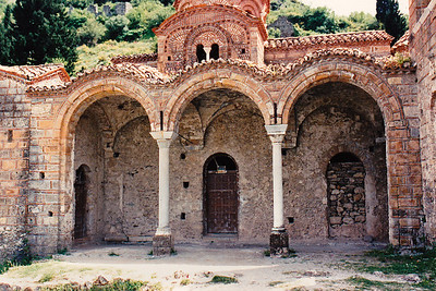 Closeup of the façade of Saint Sophia Church, Mystras. Located in the district of the Despot's Palace, it served as the palace church, the catholicon of a small monastery, and the royal tombs. Built between 1351 and 1365. Its tall, narrow structure and the use of columns in the bell tower and in support of one side of the dome is unusual for Byzantine churches of the period. During the Ottoman occupation of Mystras, the building served as a mosque, the bell tower was its minaret. The Cloisonné brickwork is more typical of Byzantine architecture.
