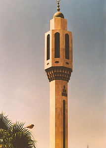 The minaret of a modern mosque crowned by a bronze hemisphere and crescent.