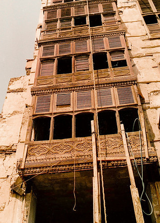 """Teakwood shuttered balconies (known either as """"shawfan"""" or """"mashrabiyya"""" in Arabic) are a traditional method of building ventilation for coping with the excessive 100-degree-plus year-round temperatures in this part of the Kingdom. This building (constructed some time in the mid-1800s) sports hand-carved panels on its faḉade."""