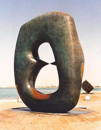 "Henry Moore's bronze sculpture ""Oval With Points"", located on a low plinth on a stretch of sidewalk on the Corniche Road. I found a recent photo of the piece wrapped in protective plastic, presumably to prevent corrosion due to the salt spray."