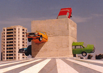 """Known locally as """"The Cars Sculpture"""", this """"assemblage"""" of Datsun sedans is embedded in a large block of unfinished concrete mounted on a large plinth situated in the center of a traffic round-about. During the Haj and Eid Al Fitir celebrations, the lights of the cars were lit at night."""