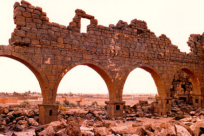 Intact arches of the West Church, Umm el Jimal.  After the Romans turned the Nabataean Kingdom into their Provincia Arabia, they also occuppied Umm el-Jimal. In A.D. 180, the Roman imperial authorities constructed a wall and a gate, a large reservoir and the Praetorium. During the 4th century A.D., in response to the rebellion of Zenobia of Palmyra, Roman armies allied with the Arab Tanoukhid Federation restored order in a destructive military campaign. At Umm el-Jimal the civilian settlement was replaced by a military garrison stationed in a purpose built fort, the early castellum, which was part of the general fortification of the Roman frontiers at the time of Diocletian and Constantine. Besides this castellum structures on the sight included the Great Reservoir, the Praetorium and a small temple.  A gradual transformation from a military station to a civilian town began as Roman imperial power waned and was then replaced by the Byzantine era. From the 5th to 8th centuries, Umm el-Jimal became a prosperous rural farming and trading town. During this period of prosperity, many residents converted to Christianity resulting in an explosion of church construction: Fifteen churches were built in the late 5th and 6th centuries. The population of Umm el-Jimal likely grew to between 6,000 and 8,000 people during this time. Evidence of this culture is found throughout the site in the form of Christian symbols on houses and churches. Paradoxically, Umm el-Jimal's age of rural prosperity came after the strictures of Roman occupation were lifted.  Umm el-Jimal's local agricultural culture continued after the Muslim conquest and under the Umayyad caliphs during the 7th century. Though the site decreased in size, some new construction took place. This construction included private houses, possible conversion of several structures into mosques, and the remodeling of the Praetorium with frescoed walls and mosaic floors. Around this time the population decreased, especially after an earthquake hit Umm el-Jimal in A.D. 749.