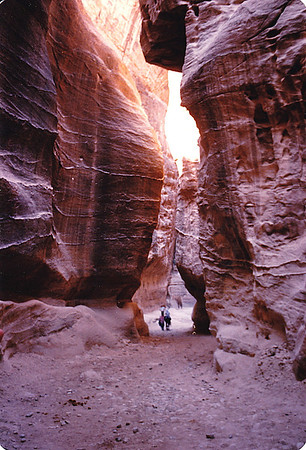 "Petra's eastern entrance leads steeply down through a dark, narrow gorge (in places only 3 - 4 m (9.8 - 13 ft) wide) called the Siq (""the shaft""), a natural geological feature formed from a deep split in the sandstone rocks and serving as a waterway flowing into Wadi Musa."