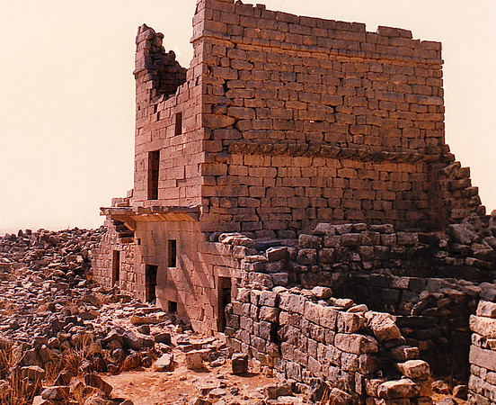 The ruin of the Roman Praetorium.  After the Romans turned the Nabataean Kingdom into their Provincia Arabia, they also occuppied Umm el-Jimal. In A.D. 180, the Roman imperial authorities constructed a wall and a gate, a large reservoir and the Praetorium. During the 4th century A.D., in response to the rebellion of Zenobia of Palmyra, Roman armies allied with the Arab Tanoukhid Federation restored order in a destructive military campaign. At Umm el-Jimal the civilian settlement was replaced by a military garrison stationed in a purpose built fort, the early castellum, which was part of the general fortification of the Roman frontiers at the time of Diocletian and Constantine. Besides this castellum structures on the sight included the Great Reservoir, the Praetorium and a small temple.  A gradual transformation from a military station to a civilian town began as Roman imperial power waned and was then replaced by the Byzantine era. From the 5th to 8th centuries, Umm el-Jimal became a prosperous rural farming and trading town. During this period of prosperity, many residents converted to Christianity resulting in an explosion of church construction: Fifteen churches were built in the late 5th and 6th centuries. The population of Umm el-Jimal likely grew to between 6,000 and 8,000 people during this time. Evidence of this culture is found throughout the site in the form of Christian symbols on houses and churches. Paradoxically, Umm el-Jimal's age of rural prosperity came after the strictures of Roman occupation were lifted.  Umm el-Jimal's local agricultural culture continued after the Muslim conquest and under the Umayyad caliphs during the 7th century. Though the site decreased in size, some new construction took place. This construction included private houses, possible conversion of several structures into mosques, and the remodeling of the Praetorium with frescoed walls and mosaic floors. Around this time the population decreased, especially after an earthquake hit Umm el-Jimal in A.D. 749.