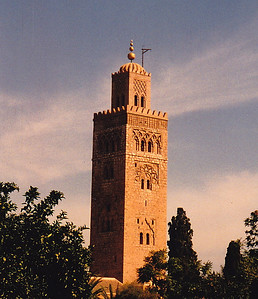 "The Koutubiyya Mosque (""Jami' al-Kutubiyah"" in Arabic) is the largest in Marrakech. It is ornamented with curved windows, a band of ceramic inlay, pointed merlons, and decorative arches. It has a large plaza with gardens, and is floodlit at night. The minaret is 77 meters (253 ft) high and is located just west of the Jemaa El Fna souq (open air-market), where I spent most of my time in the evenings I was in Marrakech. The mosque was completed under the reign of the Almohad Caliph Yaqub al Mansur (1184 to 1199 AD)."