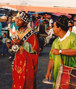 Djemaa al Fna (Marrakech) minstrels: Colorfully-dressed street musicians play hand cymbals and drums as they sing and stroll through the market-day crowd.