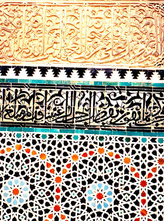 Seen in a hammam (lavatory) in a madrasa in Rabat: Porcelain mosaic tile topped by a band of porcelain panels depicting Koranic prayers in highly stylized Arabic scrikpt. The uppermost band of Arabic script is made of mudstone.