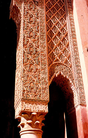 Seen in a madrasa in Marrakech: An ornate Corinthian-style column supporting a archway adorned with mosaic tiles and sculpted mudstone panels.