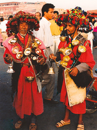 "A pair of water sellers dressed in traditional garb wander amongst the crowd in Djemaa al Fna square. All of the square's ""entertainers"" (from snake charmers to traditional no-anesthic dentists) charge to pose for tourists' photographs."