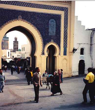"Fez, Morocco: Bab Bou Jeloud, known as ""The Blue Gate."" The minaret (the left one of the two shown) of the Madrasa (religious school) Bou Inania can be seen through the opening."