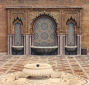 "Madrasa Bou Inania: A marble fountain surrounded by a floor of intricate porcelain tiles (foreground) and public ""hammam"" or lavatory sinks used by Muslims to perform their ablutions prior to praying in the mosque."
