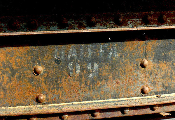 A piece of hardware on rolling stock bearing the name of the city of Haifa in white stenciled lettering.