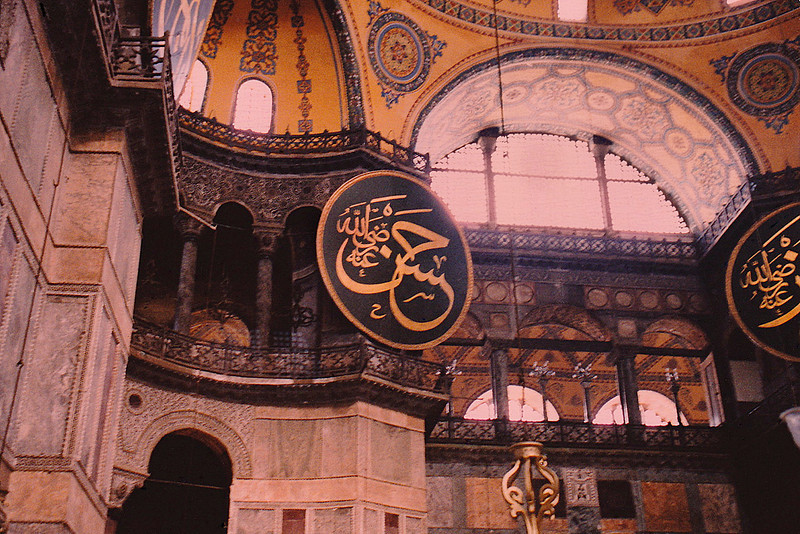 Interior of Hagia Sophia: The most famous restoration of the Aya Sofya was ordered by Sultan Abdülmecid and completed by eight hundred workers between 1847 and 1849, under the supervision of the Swiss-Italian architect brothers Gaspare and Giuseppe Fossati. The brothers consolidated the dome and vaults, straightened the columns, and revised the decoration of the exterior and the interior of the building. The mosaics in the upper gallery were cleaned. The old chandeliers were replaced by new pendant ones. New gigantic circular-framed disks or medallions (reportedly made of tanned camel hides; one can be seen in this photo) were hung on columns. They were inscribed with the names of Allah, the Prophet Muhammad, the first four caliphs Abu Bakr, Umar, Uthman and Ali, and the two grandchildren of Mohammed: Hassan and Hussain, by the calligrapher Kazasker Mustafa İzzed Effendi (1801–1877).  Link to further information about Hagia Sophia: https://en.wikipedia.org/wiki/Hagia_Sophia.