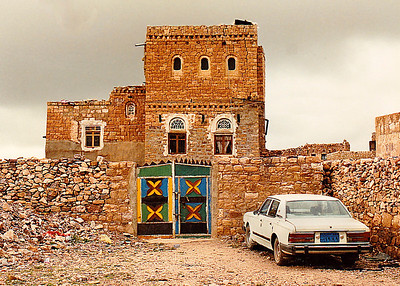 Hajarah: The brightly-colored hand-painted gate and modern sedan parked in front of this traditional home seem incongruous among the uniformly brown and tan colors of the local architecture.