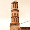 The rough stone minaret of Hajarah's lone mosque.  The arched windows of the minaret had to be bricked in to prevent the structure's collapse during the numerous earthquakes that plague this region.
