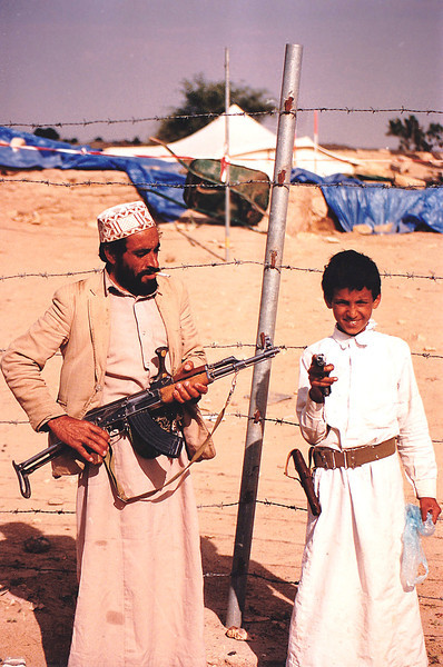 My driver (man on the left holding the AK 47) poses for the camera with the young boy guarding one of the active archeological excavations outside Awwam. Oddly enough, both weapons belonged to the boy guard! Every male in Yemen seemed to own a hand gun or AK 47 rifle.