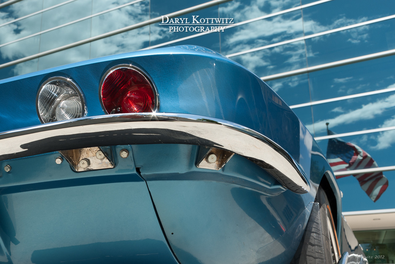Blue Vette.  Shot at a company car show in 2009.  I like the reflection of Old Glory in the background.