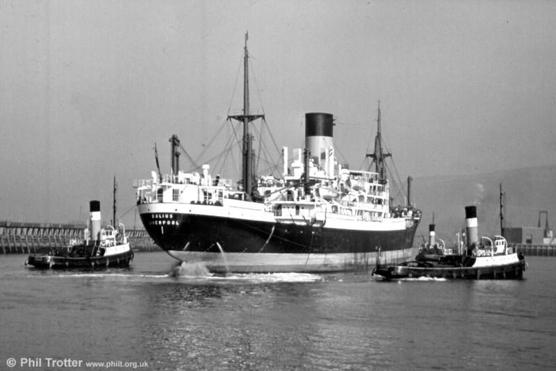 <DIV ALIGN=left>The classic 'China Boat'; Blue Funnel Line's Dolius being attended to by the Swansea tugs. Dolius was a 'Mark A5' ship built in 1955 by Harland & Wolff at Belfast with a tonnage of 7960grt and a service speed of 15 knots. She was transferred to Glen Line and renamed Glenfruin in November 1970 and reverted to Holt's (Blue Funnel) and her former name in April 1972. In the following November she was sold to Nan Yang Shipping Co. of Macao and renamed Hungmien. She was later sold to the Bureau of Maritime Transportation of Canton, China and renamed Hong Qi. Subsequently renamed Zhan Dou, she was based at Guanzhou under the same owners. Her eventual demise is unknown but she was deleted from Lloyds Register in November 1991.</DIV>