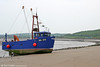Far from its registered home port of Boston, Lincs., the 2000-built mussel and cockle dredger 'Tricia B' has taken up residence on the beach at Ferryside. The boat's claim to fame is that in June 2005 it lost its anchor and went aground on the rocks to the east of Burry Port Harbour; Burry Port Lifeboat was called out to assist. Meanwhile, an unidentified ATW class 175 passes in the distance, forming the 1323 Milford Haven to Manchester Piccadilly on 1st May 2011.