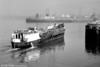 A small coastal barge, M.V. Glassmaker, emerges from the sea fog to enter Swansea Docks via the Kings Dock Lock Entrance in the 1960s.