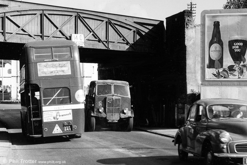 AECs (and Guinness) are Good For You... Two AECs at work in 1963; South Wales Transport AEC Regent III/Weymann L27/26R 1141 (GCY 541) heads under a low railway bridge at Neath, while a Rosser, Pontlliw Mammoth Major, JNY 484, comes in the other direction.