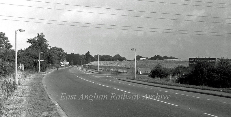 The old route of the B1049 Cambridge to Histon Road on 11th September 1977. Compare this to the fourth photo in this section. The field to the right is now filled with earthworks and the bank of the Westbound slip road can be seen. A blue sign has gone up to the right advertising the construction of the A45 Cambridge Northern Bypass.