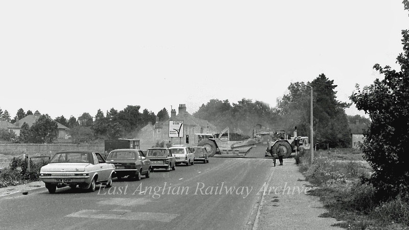 A line of ancient cars are held up at temporary traffic lights by the passage of a massive earth mover across the old B1049. The view is looking towards Histon with the houses on Lone Tree Avenue on the left.  17th July 1977